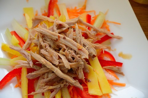 Shredded duck meat on a bed of julienned mango, carrot and celery