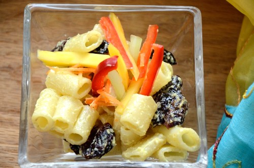 Bombay Pasta salad in a dish with mango and red pepper garnish