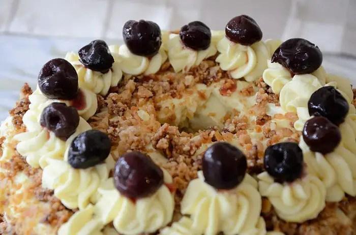 German Frankfurter Wreath cake with black cherries on buttercream rosettes around top of cake