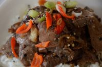 Close up of Flank steak strips with pepper and green onion garnish in black pepper sauce.