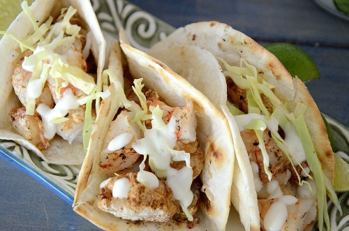 Three grilled shrimp tacos with lime crema garnish