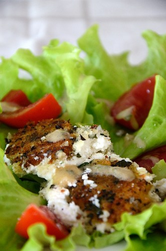 Crispy goat cheese rounds on bed of lettuce with tomato