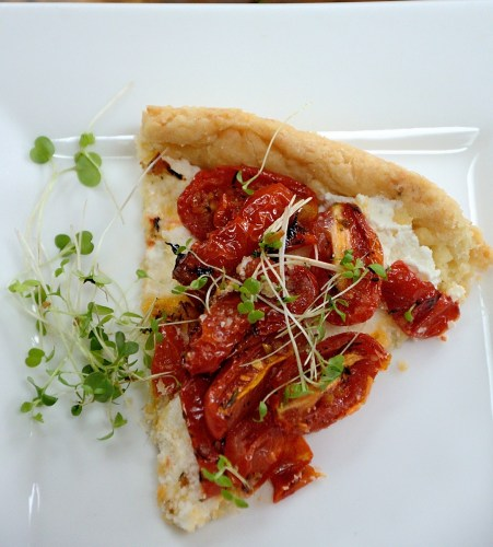 Piece of tart filled with roasted tomatoes and garnished with microgreens