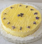 Ricotta cake on a bed of icing sugar decorated with candied violets