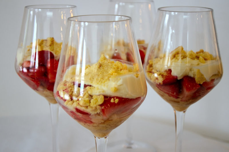 Four stemmed glasses filled with strawberries, mascarpone cream and topped with amaretti crumbs