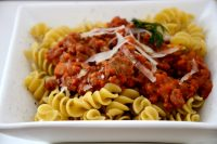 Dish or fusilli pasta with sausage and fennel sauce and fresh parmesan garnish