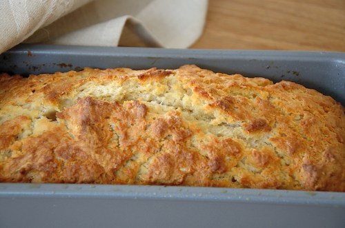 loaf of beer bread in a loaf pan with a golden crusty top