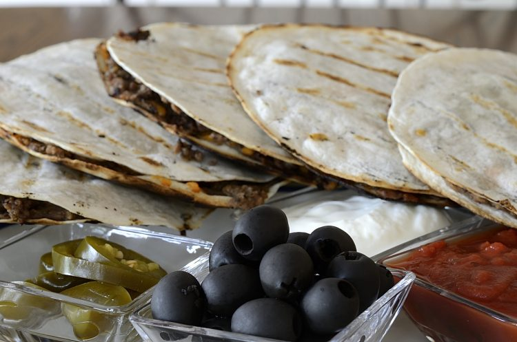Grilled black bean quesadillas on a platter with black olives, salsa and jalapeno peppers for garnish