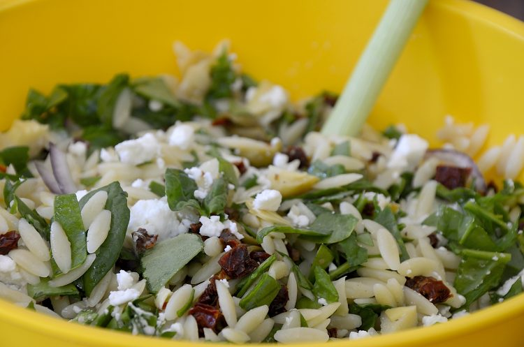 Spinach, orzo, artichoke hearts, goat cheese and sun dried tomatoes tossed in a bowl.