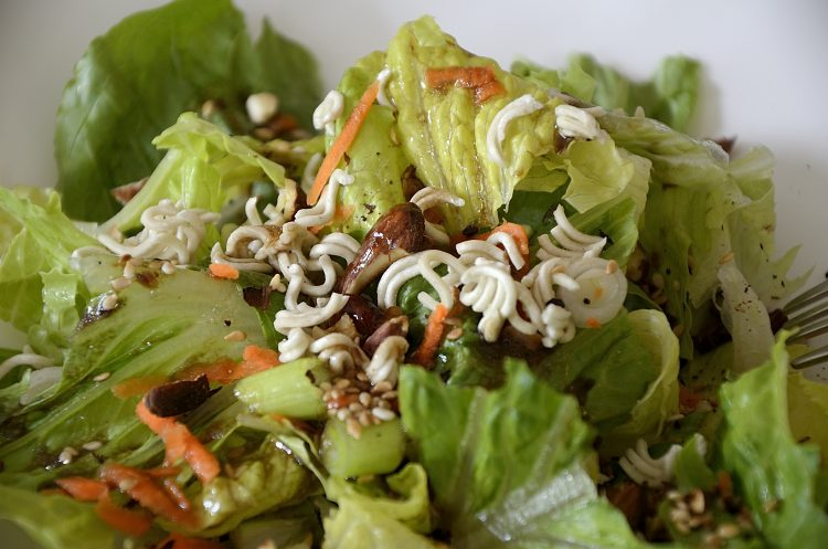 Romaine lettuce with oriental dressing, toasted sesame seeds, almonds and green onions