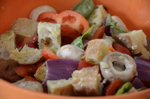 Sausage, pepper, onion and mushroom pieces marinating in dressing in a large bowl.