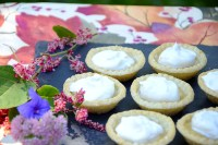 Maple tarts with whipped cream topping on a tray on an autumn table cloth.