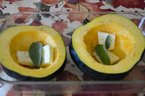 Two roasted acorn squash halves with butter and sage.