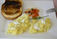 Softly scrambled eggs topped with goat cheese and fresh dill.
