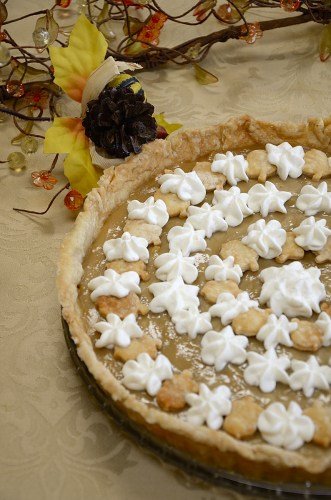 Maple Cream Tart decorated with acorn pastry cutouts and whipped cream.