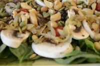 Salad on platter covered in cashews, pumpkin seeds, caramelized onions, grape tomatoes and sliced mushrooms.