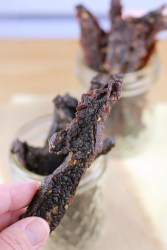 Slices of dried beef jerky standing upright in a jar.