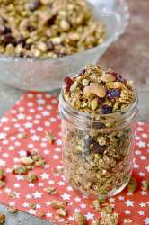 Jar of granola with almonds, cranberries, pumpkins seeds and oats.