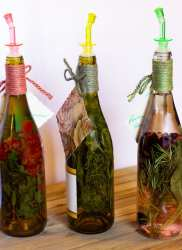 Three wine bottles filled with herbs and fruit with colourful stoppers.