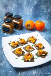 Tray of appetizers with persimmon chutney dabbed on cheese on cracker. Persimmons and jars of chutney in background.