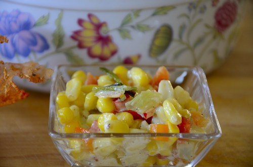 Colourful serving bowl of yellow corn, orange and red peppers and grilled green onions.