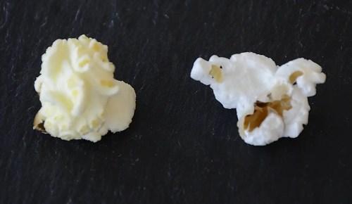 Close up of round mushroom popped corn kernel on left and popped butterfly popcorn kernel on the right.