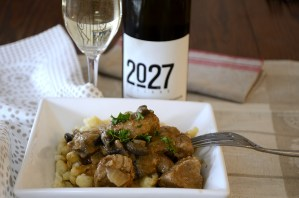 Place setting with a dish of juicy, creamy cubes of cooked pork and mushrooms over German Spatzle noodles and a glass of white wine on the side.