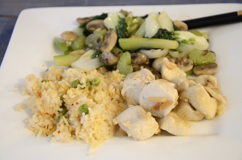 Serving plate with lemoncello chicken, rice, and stir fried baby bok choy with chop sticks.