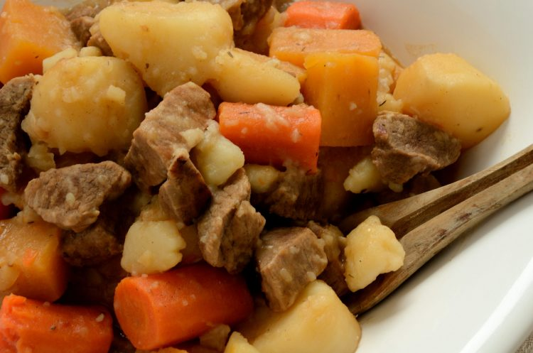 Close up of stewed beef cubes, carrots and potatoes.