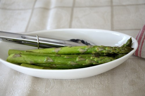 Spears of asparagus in a dish fresh from the air fryer.
