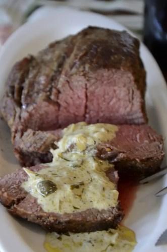Beef tenderloin sliced with Cafe de Paris sauce spooned over.