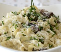 Egg noodles with creamy ricotta, lemon sauce, asparagus, mushrooms and garnished with chives.