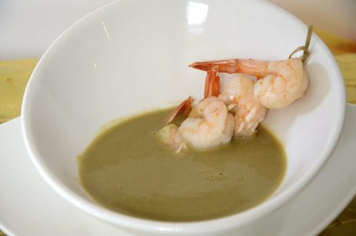 Asparagus soup in a white bowl with a skewer of shrimp.