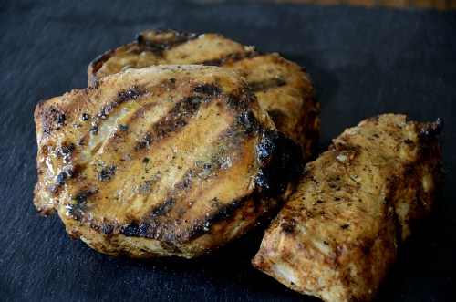 Thick golden, juicy pork chops with dark grill marks.
