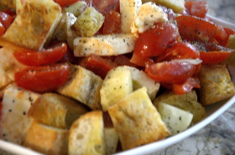 Rustic toasted croutons with chopped tomatoes for panzanella salad.