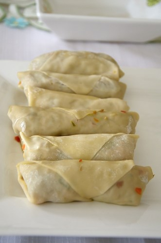 Uncooked egg rolls on a platter.