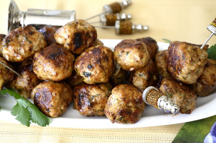 Crispy, browned lemon turkey meatballs on a platter with serving picks.
