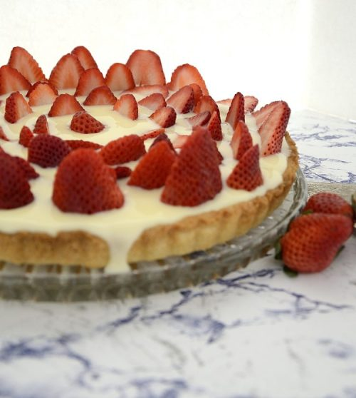 Round tart with crust filled with vanilla pudding and topped with circles of sliced strawberries.