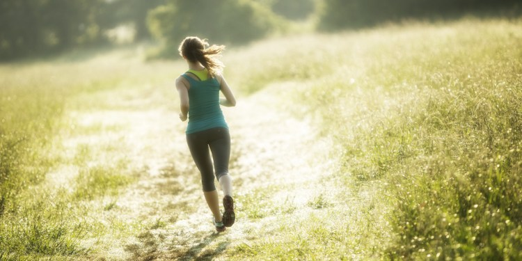 Woman jogging through a field