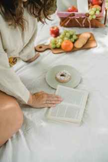 a woman, reading a book and eating fruit  hobbies