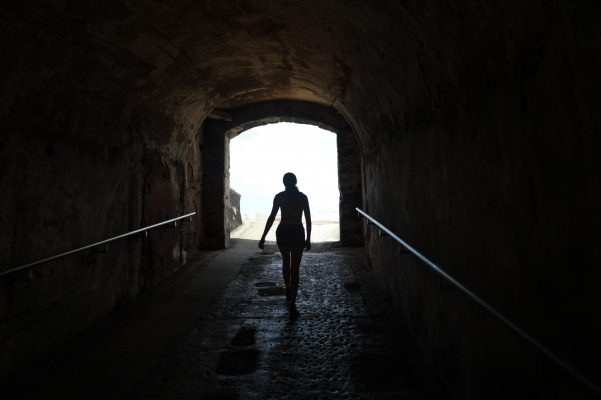 silhouette of person walking on tunnel