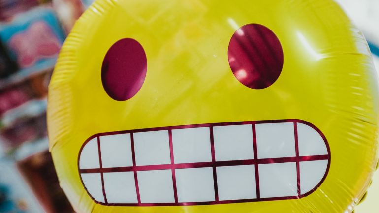 yellow inflatable smiling emoji balloon in focus photography
