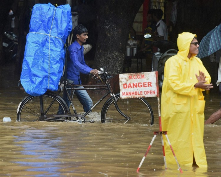 People wade through a water logged road after heavy rains in Mumbai on Saturday. PTI Photo by Shashank Parade