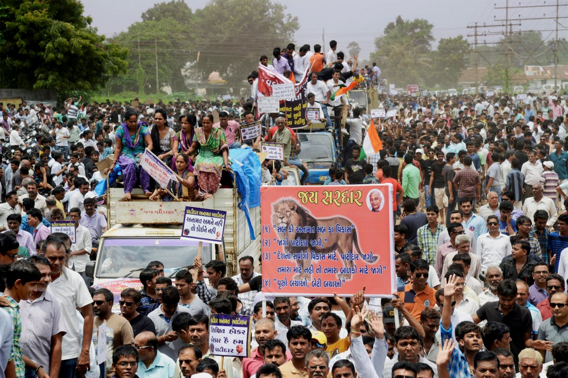 People from Patidar or Patel community hold placards and shout slogans during a protest rally demanding reservation for their community in Vadodra on Friday. Credit: PTI