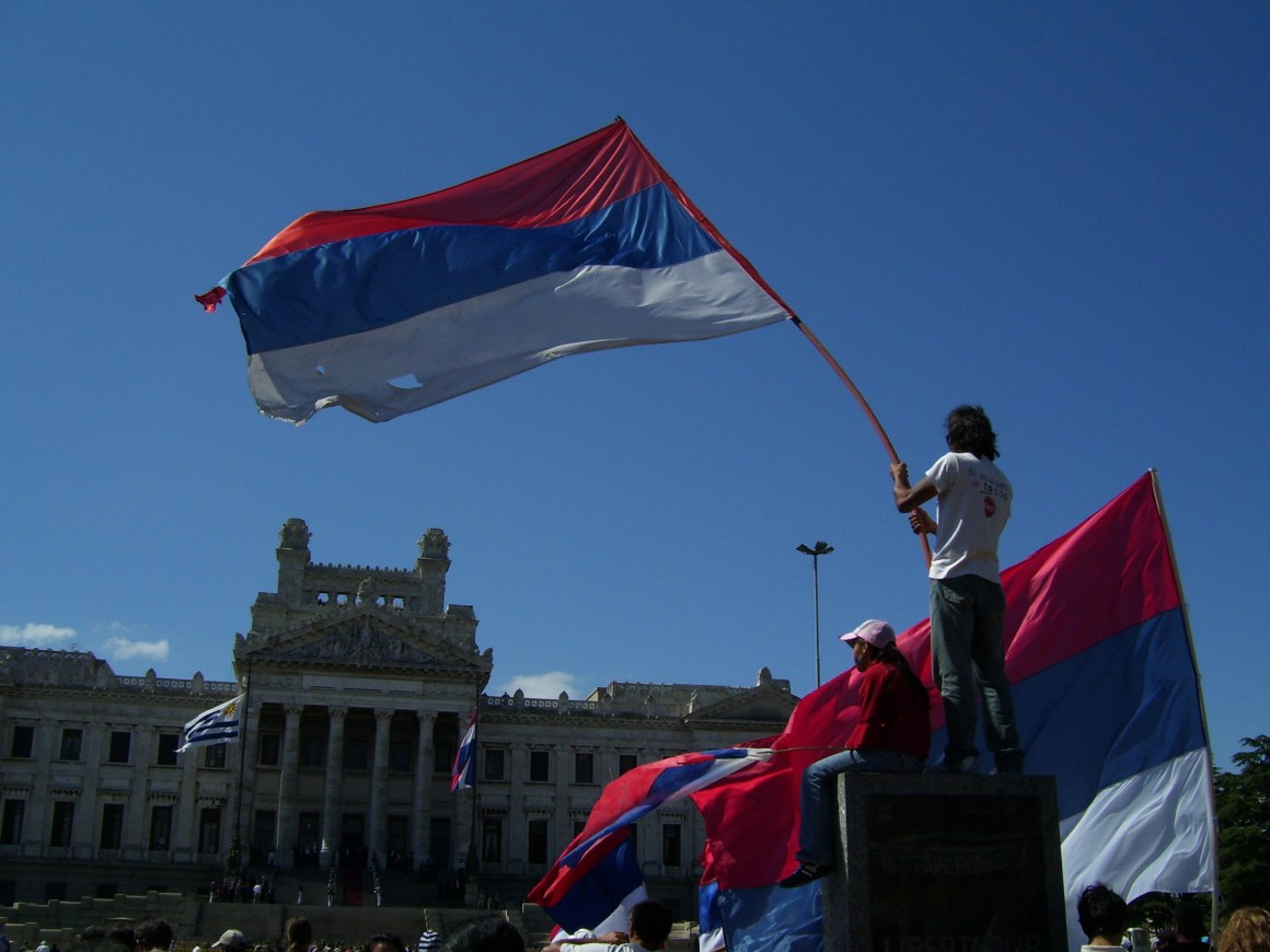 Flag of the Frente Amplio being waved in front of the Legislative Palace of Uruguay. Credit: Wikimedia Commons, CC BY 3.0