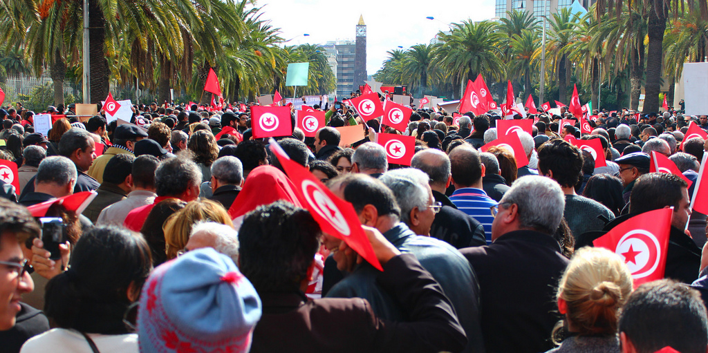 A crowd of people waving the Tunisian flag. Credit: nystagmus/Flickr, CC BY-NC 2.0