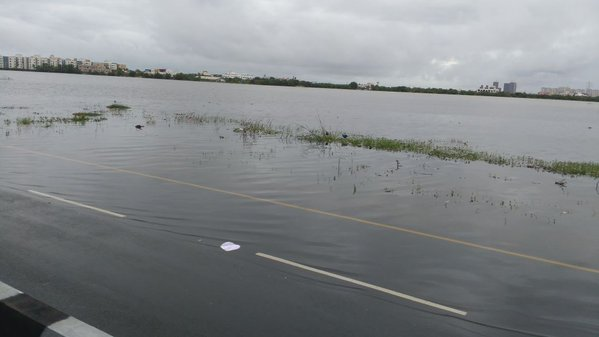 A lake in Perumbakkam breached following heavy rains, flooding neighbouring roads and an SEZ. Credit: Tirusenthil