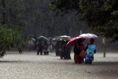 Staffs and visitors move from a flooded Government hospital after heavy rains in Chennai on Tuesday. Credit: PTI