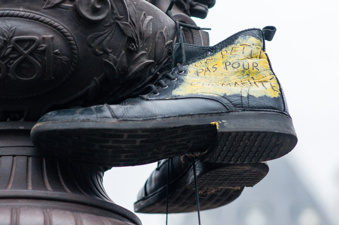 A giant pair of shoes hangs from a fountain at the Place de la Republique in symbolic protest at the ban on public protests in Paris during the ongoing climate change conference. Credit: Duc/Flickr
