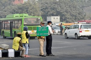 Civil defence volunteers holding a placard as traffic policeman takes protection against pollution in New Delhi. Credit: PTI